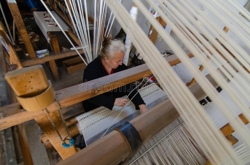 Traditional hand weaving in the Kastamonu in Turkey. Kastamonu,TURKEY-November 05,2017: Woman working at the loom. Turkey national crafts, top view royalty free stock photo