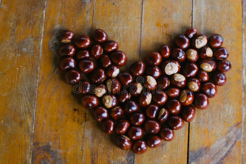 Kastanien, die ein Herz auf einem hölzernen Hintergrund bilden lizenzfreies stockfoto