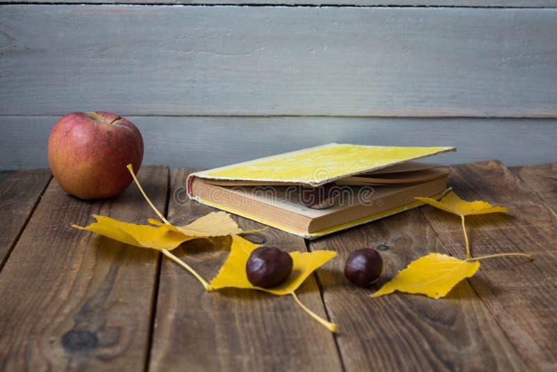 Kastanj för sidor för bokäpple en gul på träbakgrund royaltyfri foto