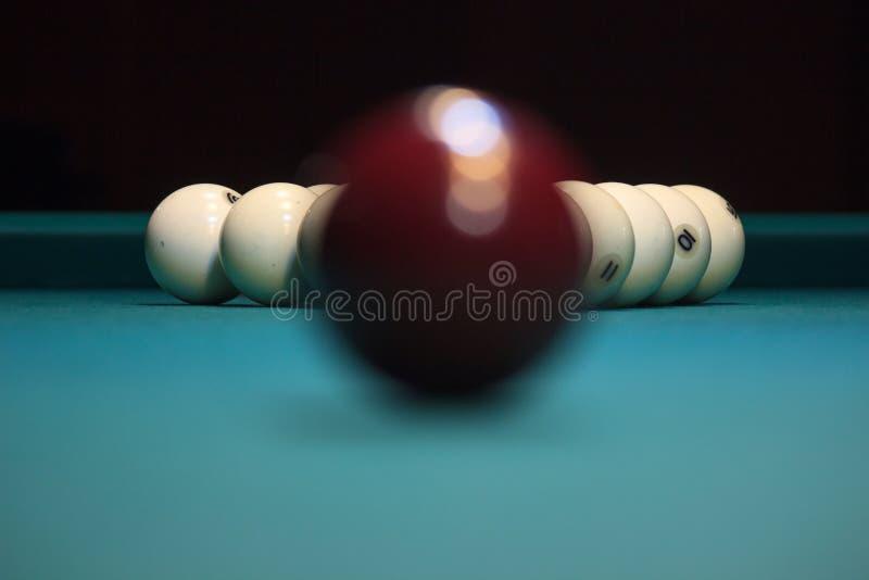 Kastanjebruine bal die op een groene poollijst liggen de tijd vóór het spel de bezinning van de lamp in de kom stock fotografie