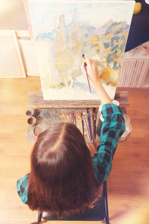 Kastanjebrun haired flickamålning med olje- flåsanden arkivfoton