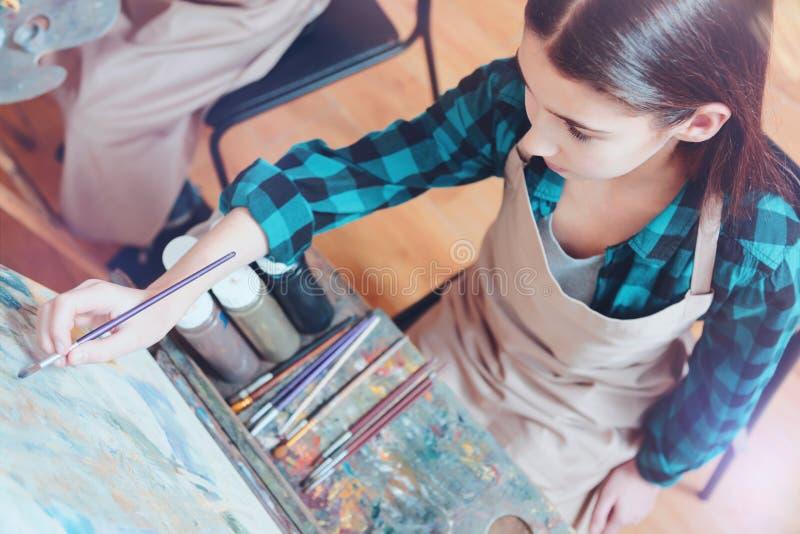 Kastanjebrunt haired flickasammanträde på staffli, medan måla royaltyfria foton