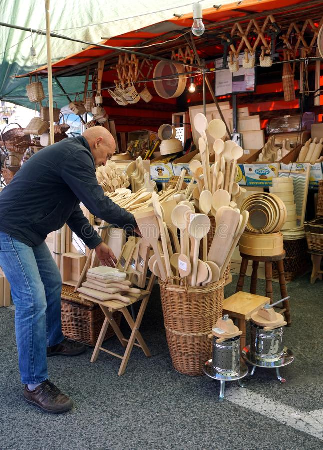 A man whose arranges wood products in his street shop on the town fair royalty free stock images