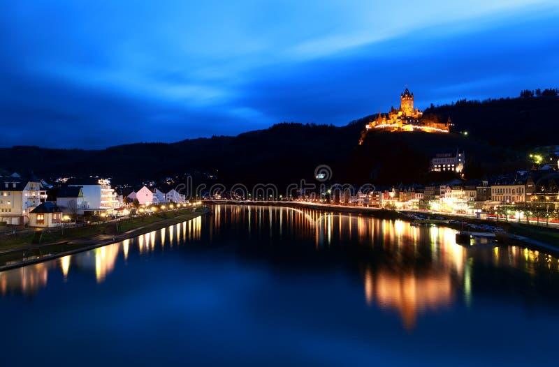 Kasteel dat in rivier bij nacht wordt weerspiegeld stock afbeelding