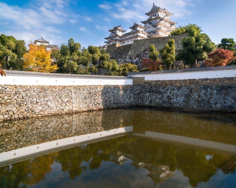 Kasteel van Himeji in de herfst dacht in het vijverwater na bij de bodem van zijn versterkte muren royalty-vrije stock afbeeldingen