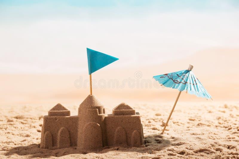 Kasteel in zand, vlag en parapluclose-up op overzees stock foto