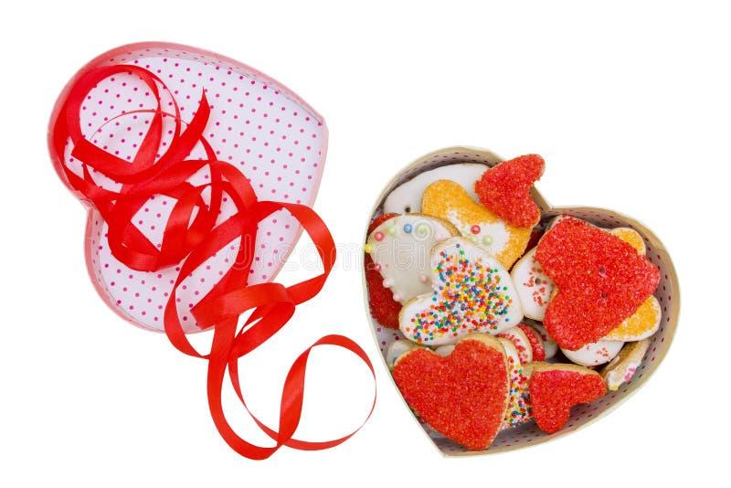 Kasten mit buntem selbst gemachtem Herzen des Feiertags formte die Plätzchen und rotes Band, die auf weißem Hintergrund mit Besch stockfotografie