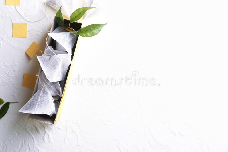 Kasten mit Teebeuteln auf weißem strukturiertem Hintergrund lizenzfreie stockfotos