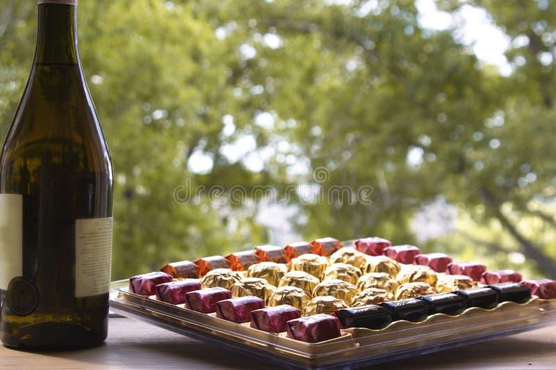 Kasten von Schokoladen und von Flasche Wein auf dem Hintergrund der Natur lizenzfreie stockfotografie