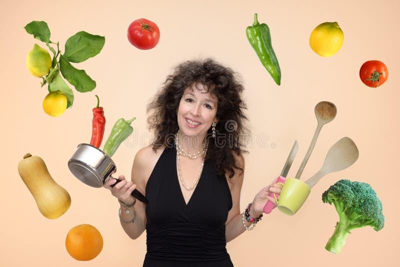 Kastrull för kvinna som 50+ flyger grönsaker och frukter royaltyfria foton