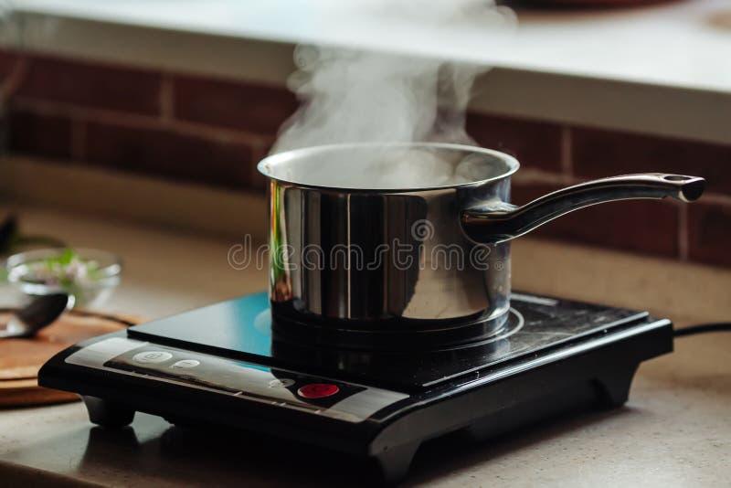 Kastrull med koka vatten på den elektriska kökugnen arkivbild