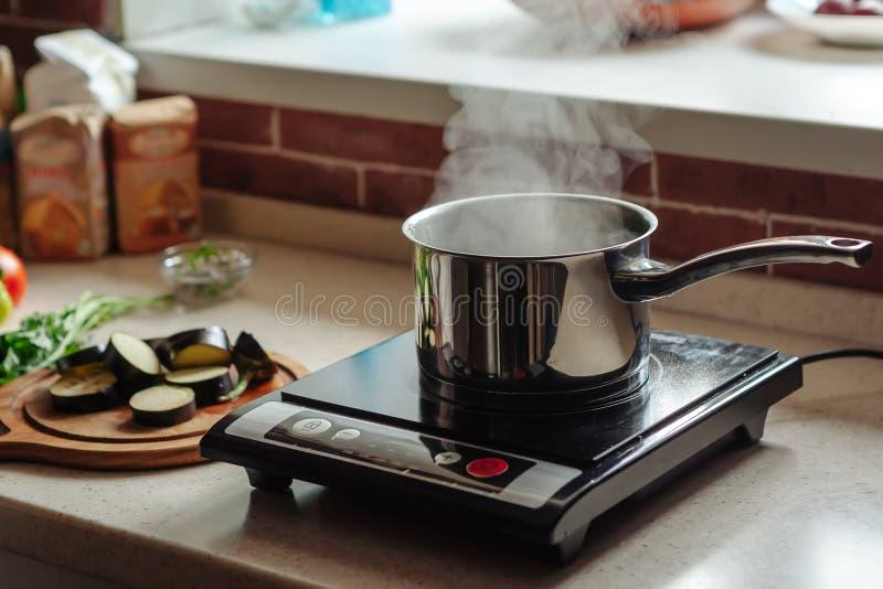 Kastrull med koka vatten på den elektriska kökugnen Aubergine-, peppar- och tomatlögn på tabellen i arkivbilder