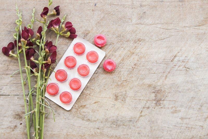 Kaszlowa bolesnego gardła trociczka kolorowa i flowerw na stole zdjęcie stock