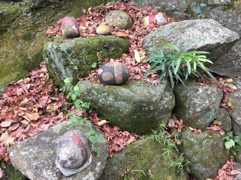 Kat het schilderen op ronde stenen met esdoorn doorbladert stock afbeeldingen
