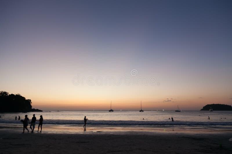 Kata bonito phuket da praia em Tailândia na ilha do puhket Silhuetas dos povos no por do sol No primeiro plano é a silhueta de foto de stock