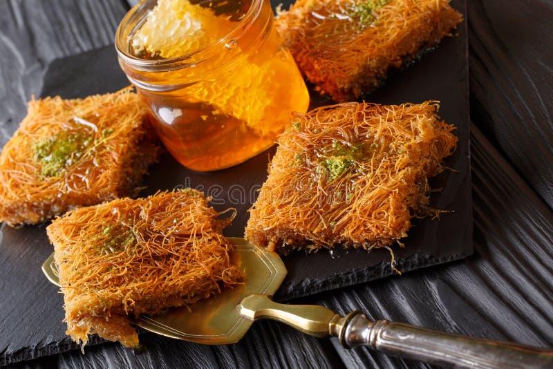 Kataifcake met pistaches en verse honingsmacro op een lijst Ho stock foto's