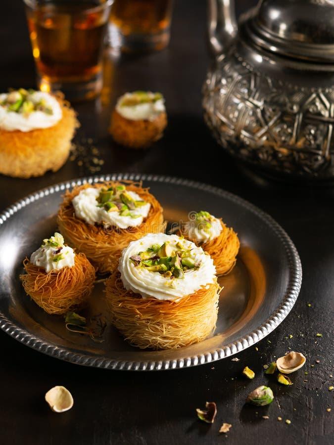 Kataifi, kadayif, kunafa, Baklavagebäck-Nestplätzchen mit Pistazien mit Tee Kochen des Bonbontürkischen oder arabisches tradition lizenzfreie stockfotos