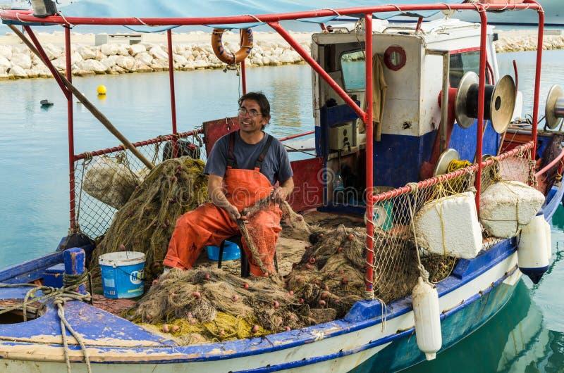KATAKOLO GREKLAND - Oktober 31, 2017: Den grekiska fiskaren som analyserar förtjänar i en fiskebåt royaltyfria bilder