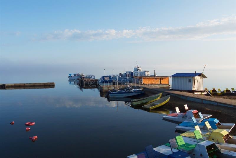 Katamaran och fartyg i den dimmiga morgonen på sjön royaltyfria bilder