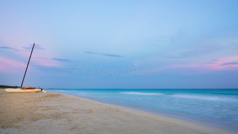 Katamaran på solnedgången på stranden arkivbild