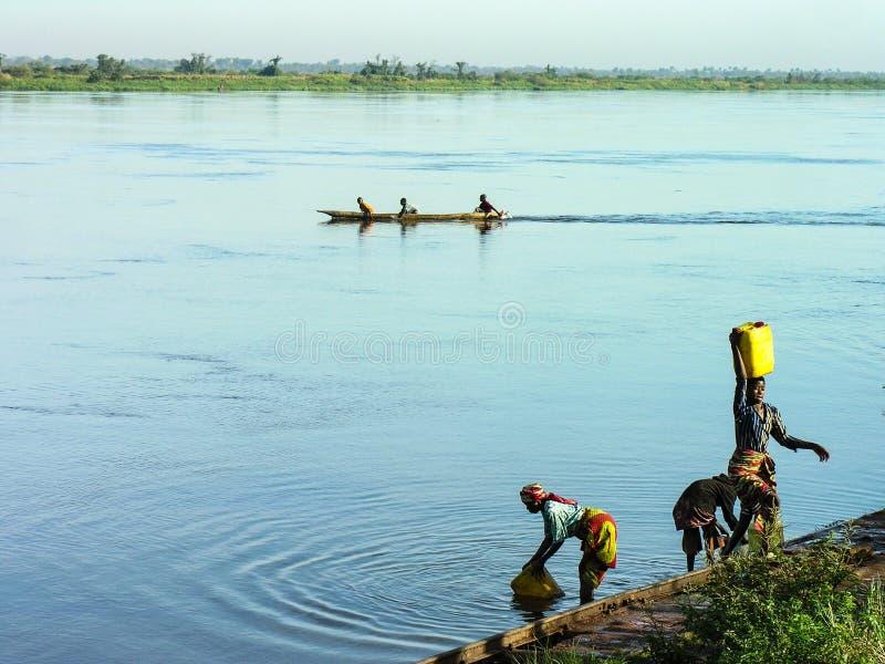 Katanga DRC, 11th Juni 2006: Kvinnor som hämtar vatten från flodKongofloden royaltyfria bilder