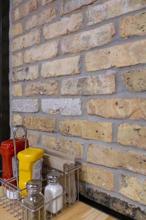 Katchup, musztarda, sól, pieprz i pieluchy obok ściany z cegieł, obrazy stock