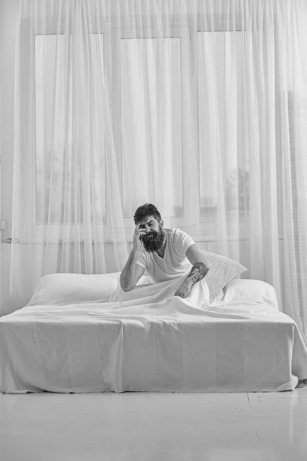 Katerconcept Kerel op teleurgestelde pijnlijke gezichtsontwaken in ochtend De mens in overhemd zit op bed wakker, wit gordijn stock fotografie