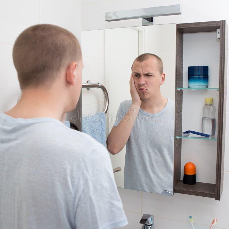 Katerconcept - vermoeide mens die spiegel in badkamers bekijken royalty-vrije stock afbeelding