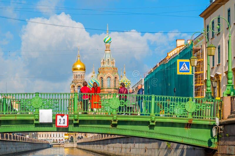 Kathedraal van Onze Verlosser op Gemorst Bloed en Italiaanse brug met toeristen die op de oriëntatiepunten van St. Petersburg let stock afbeelding