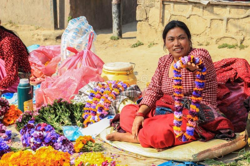 Nepalese woman seller in elegant sari sells flower wreaths at Kathmandu street market royalty free stock image