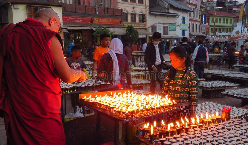 Buddhist monk lights a praying candle, Boudhanath stupa, Kathmandu, Nepal. Kathmandu, Nepal - 11/13/2017: Buddhist monk lights one of the many praying candles royalty free stock photo