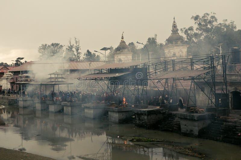 Kathmandu, Nepal - 1º de janeiro de 2017: O desbarbamento de povos inoperantes no fogo santamente foto de stock royalty free