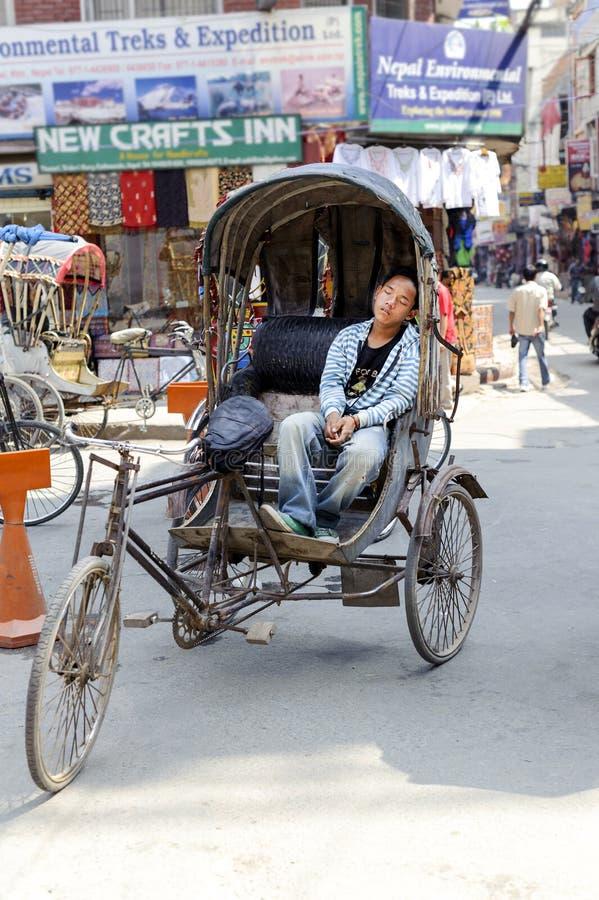 KATHMANDU, NEPAL - 17 DE MAIO DE 2014: Motorista cansado do riquexó de ciclo que dorme em seu veículo na entrada da área Kathmand fotografia de stock