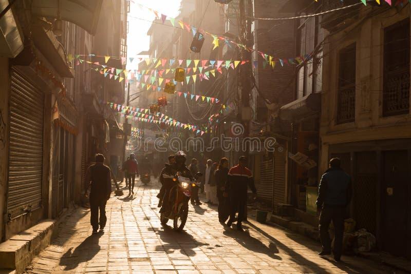 Kathmandu, Nepal - 17 de novembro de 2018: Amanhecer em Kathmandu Povos Nepali que vão abaixo da rua no distrito de Thamel fotografia de stock