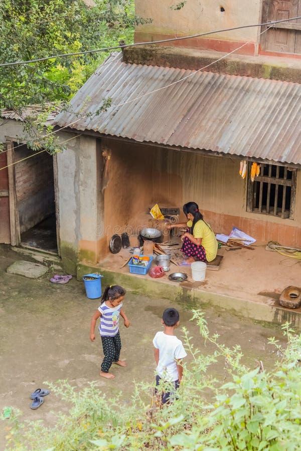 Kathmandu, Nepal - 4 de novembro de 2016: Duas crianças nepalesas que jogam na frente da casa quando sua mãe que prepara a refeiç imagem de stock