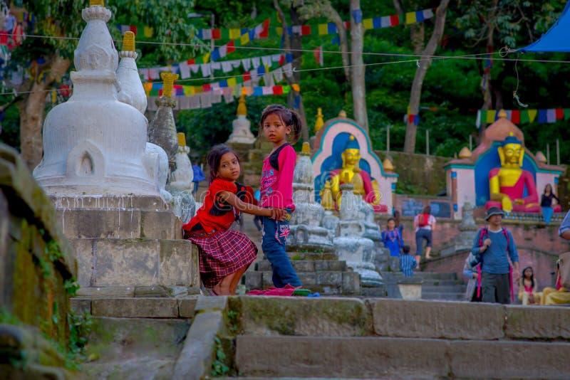 KATHMANDU, NEPAL 15 DE OUTUBRO DE 2017: Crianças não identificadas que sentam-se no ar livre perto de Swayambhu, um religioso ant imagens de stock