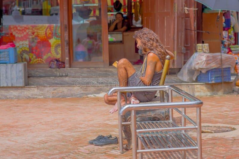 KATHMANDU, NEPAL 15 DE OUTUBRO DE 2017: Homem não identificado, sem abrigo que leem um livro no assento fora em um público metáli imagem de stock