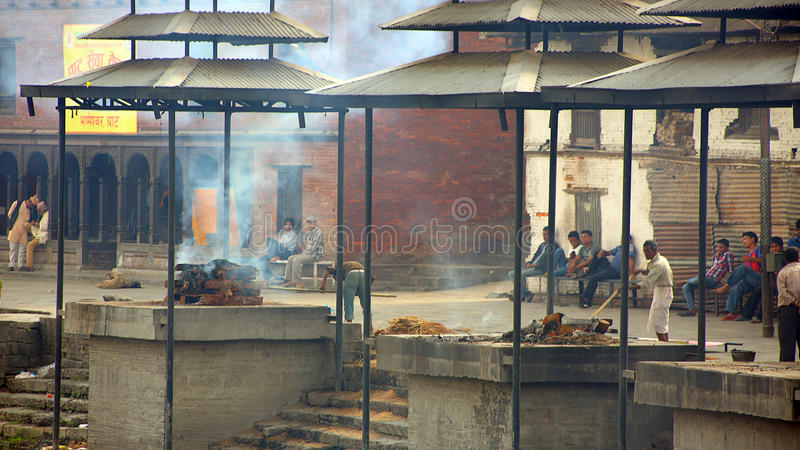 KATHMANDU, NEPAL - JUNE 2013: cremation at pashupatinath temple. KATHMANDU, NEPAL - JUNE 2013: death corpse burning in fire, cremation ceremony at pashupatinath royalty free stock images