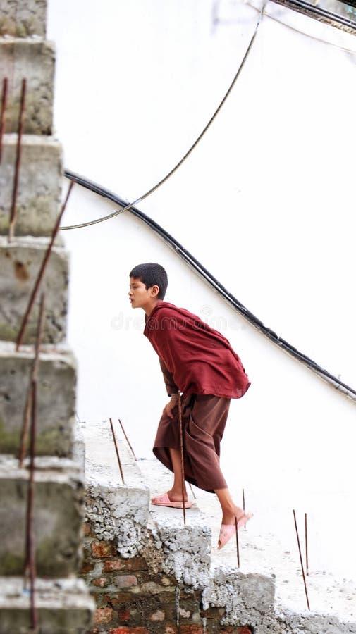 Buddhist monk climbing stairs royalty free stock image