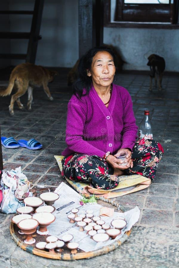 KATHMANDU NEPAL, KWIECIEŃ, - 2015: stara kobieta sprzedaje świeczki w Swayambhunath świątyni zdjęcia royalty free