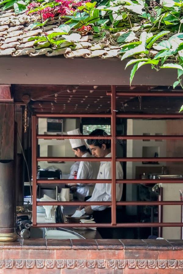 Kathmandu Nepal, Listopad, - 03, 2016: Widok Nepalski szef kuchni i sous szef kuchni pracuje w kuchni przez okno zdjęcia stock
