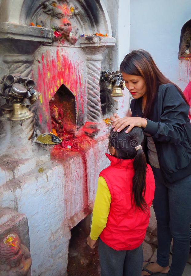 Mother painting a little red dot called tika on the forehead of her child at Boudhanath stupa, Kathmandu, Nepal. Kathmandu, Nepal - 11/14/2017: Mother applying royalty free stock images