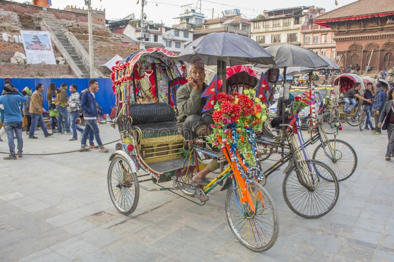 Nepali male driver of a decorated rickshaw in a street parking, talking on the phone waiting for. Kathmandu/Nepal - 14.11.2018: Nepali male driver of a decorated royalty free stock images