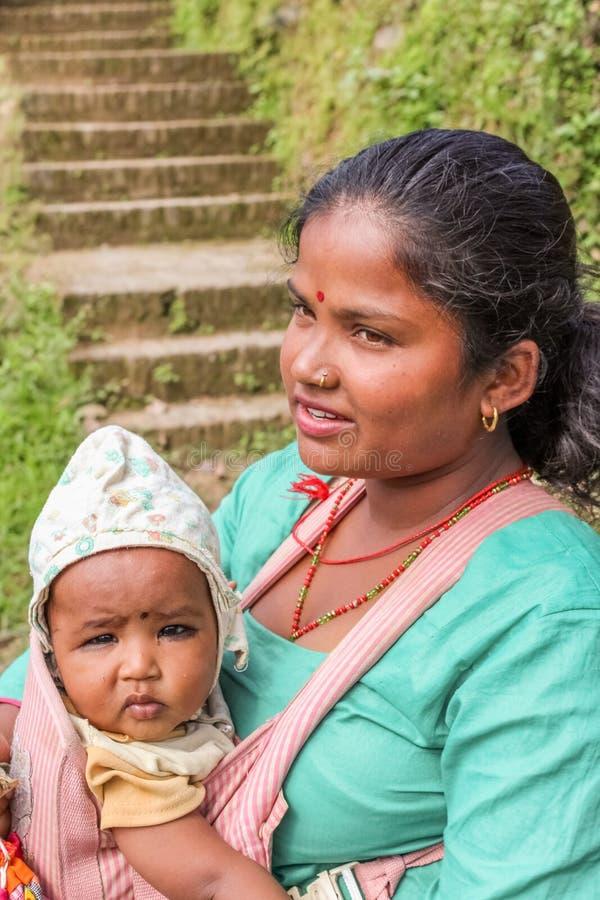 Kathmandu, Nepal - 4 novembre 2016: Giovane madre nepalese che porta il suo bambino nel villaggio, Nepal immagini stock libere da diritti