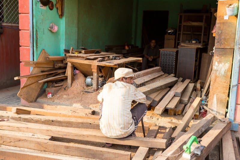 Kathmandu, Nepal - 4 novembre 2018: Uomo che lavora in un piccolo negozio dei materiali da costruzione in via centrale di Kathman immagine stock libera da diritti