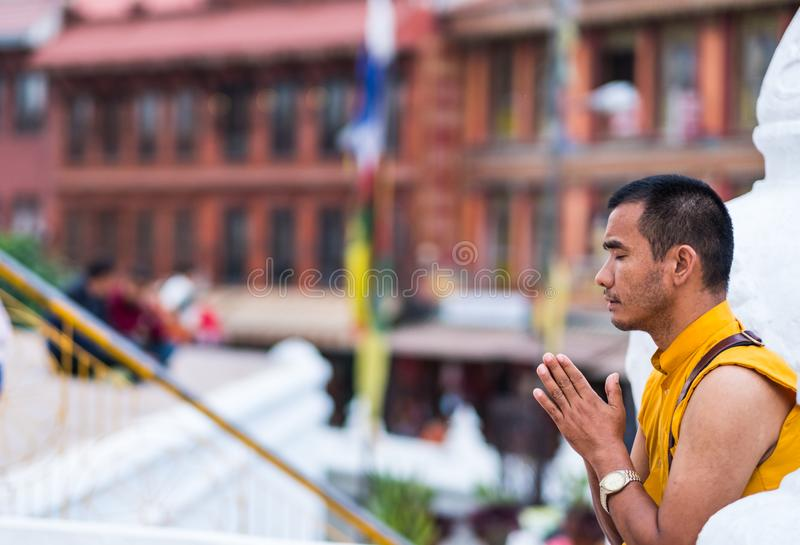 Tibetian monk prays on the Boudhanath Stupa, Kathmandu royalty free stock photography