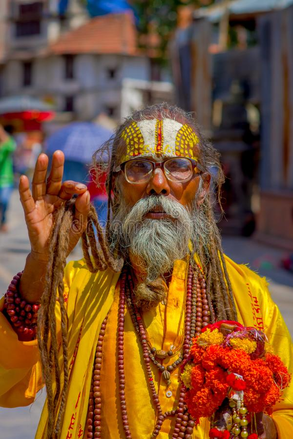 KATHMANDU, NEPAL OCTOBER 15, 2017: Portrait of Nepalese sadhu man holding in his hands a prayer beads on the street of. Kathmandu square in Nepal stock images