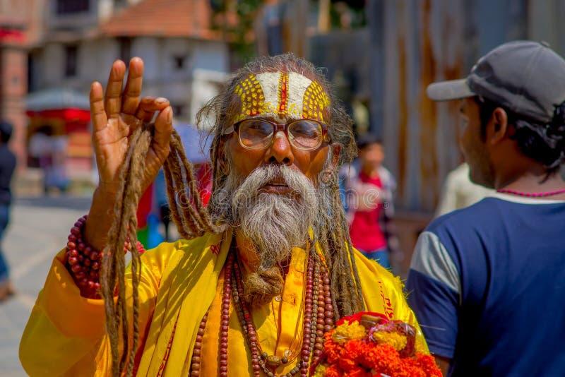 KATHMANDU, NEPAL OCTOBER 15, 2017: Portrait of Nepalese sadhu man holding in his hands a prayer beads on the street of. Kathmandu square in Nepal royalty free stock image