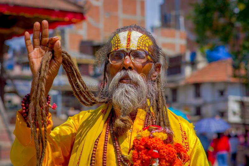 KATHMANDU, NEPAL OCTOBER 15, 2017: Portrait of Nepalese sadhu man holding in his hands a prayer beads on the street of. Kathmandu square in Nepal royalty free stock photography