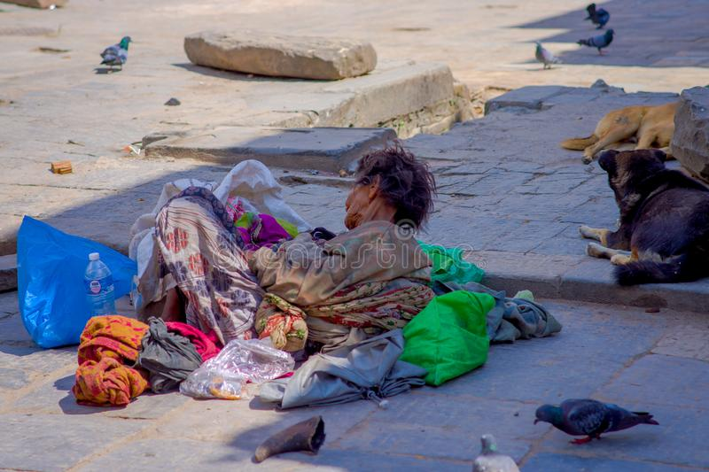 KATHMANDU, NEPAL OCTOBER 15, 2017: Unidentified nepalese homeless laying in the ground of the streets, wearing dirty. Clothes at outdoors in a Durbar square royalty free stock images